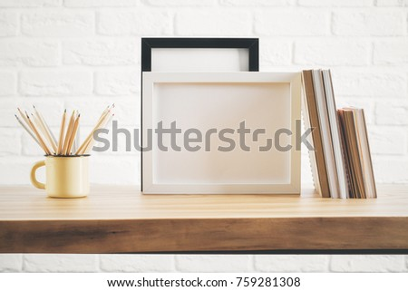 Front view of wooden desk top with empty picture frame, notepads and iron mug with pencils. Decor, decoration and style concept. Mock up  #759281308