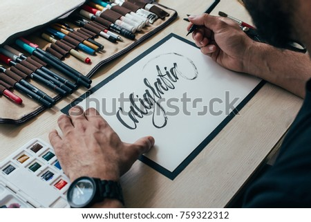 View on big sheet of white paper canvas with word calligraphy spelled on top using brush with black ink by font designer or creative artist freelancer working on project in home studio #759322312