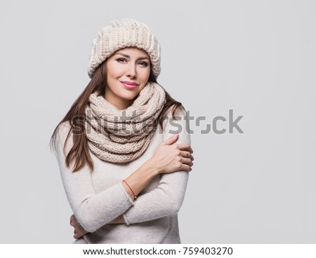 Beautiful woman winter portrait. Smiling girl wearing warm clothes #759403270