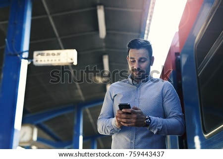 Smiling young man at the train station using smart phone #759443437
