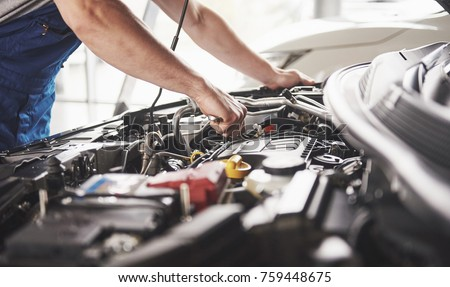 Auto mechanic working in garage. Repair service. Royalty-Free Stock Photo #759448675
