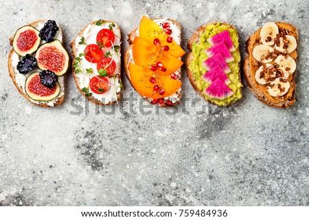 Healthy breakfast toasts with peanut butter, banana, chocolate granola, avocado, watermelon radish, persimmon, pomegranate, chia seeds, tomato, figs, blackberry. Copy space #759484936