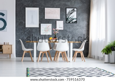 Wooden dining table with white design chairs under window and concrete wall with paintings