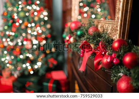 Closeup of red and green bauble hanging from a decorated Christmas branch. abstract background with defocused lights #759529033