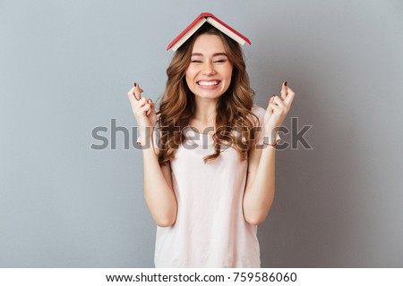 Portrait of a happy girl holding book on her head with crossed fingers for good luck isolated over gray wall background #759586060