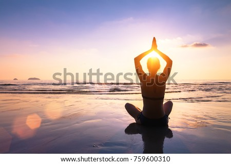 Yoga and meditation on the calm peaceful beach at sunset, fit young woman Royalty-Free Stock Photo #759600310