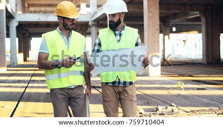 Team of construction engineers working on building site #759710404
