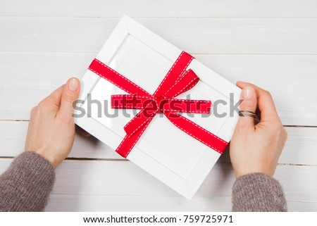 Woman's holding a gift wrapped blank frame over a wooden background