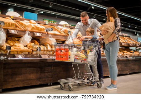 Full length portrait of happy young family shopping for groceries in supermarket together with little boy, while choosing fresh bread loaf in bakery department #759734920