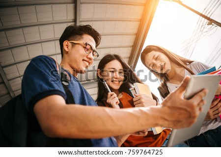 A group of young or teen asian student in university smiling and reading the book and look at the tablet or labtop computer in summer holiday. #759764725