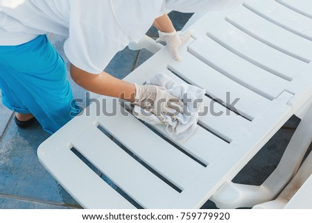 worker at the hotel removes the water from the deck chairs after the rain #759779920