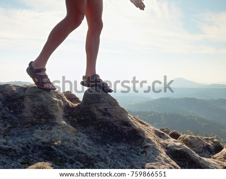 Long tired naked legs in hiking sandals on peak. Hiking in sandstone rocks, hilly landscape in blue misty cloud in background.  #759866551