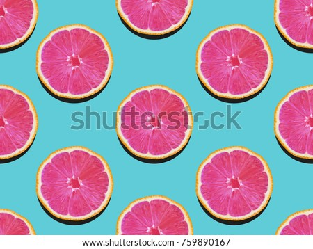 Grapefruit in flat lay Fruity pattern of grapefruit with pink flesh on a turquoise background Top view Modern flat lay photo pattern in pop art style #759890167