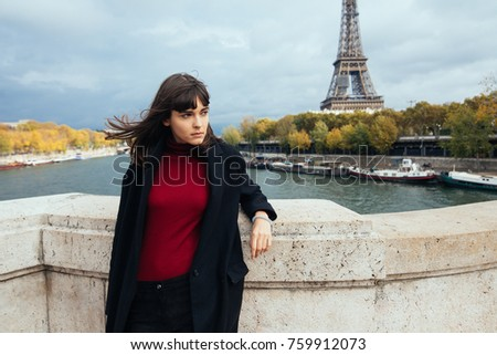 Elegant woman standing in a park with Eiffel Tower on the background #759912073