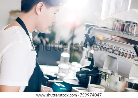 portrait  of young waiter making cup of coffee at coffee shop. #759974047