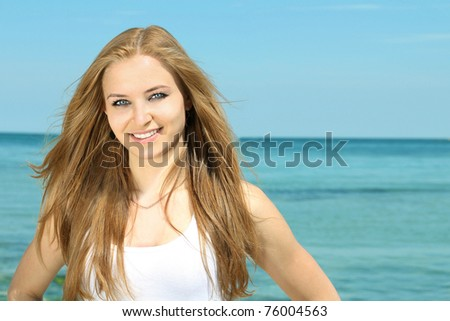 Portrait of a beautiful smiling young lady on the beach background #76004563
