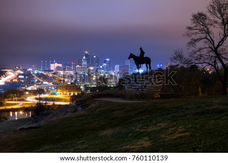 A skyline view of Kansas City, Missouri during the twilight hours with overcast skies