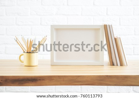 Front view of wooden desk with empty poster, notepads and iron mug with pencils. Decor, decoration and style concept. Mock up  #760113793