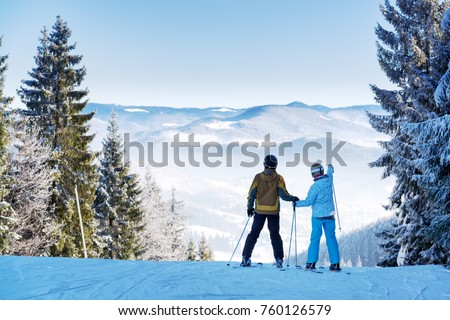 Couple of skiers watching beautiful landscape of a winter resort #760126579