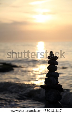 Sunset at the sea with stone pyramide in the foreground #760131817
