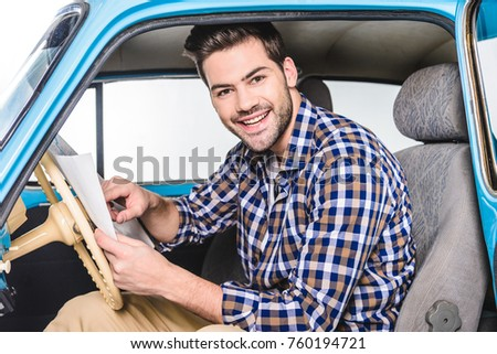 handsome young man sitting in car with map isolated on white #760194721