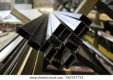 a bundle of long steel square pipes of black metal with a small rust #760197733