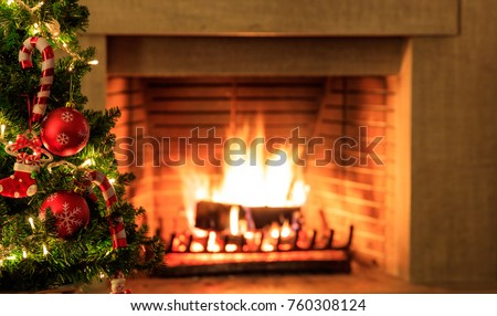 Christmas tree close up on blurred burning fireplace background