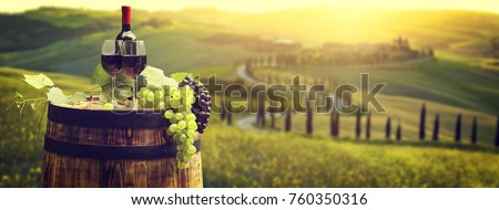 Red wine bottle and wine glass on wodden barrel. Beautiful Tuscany background #760350316