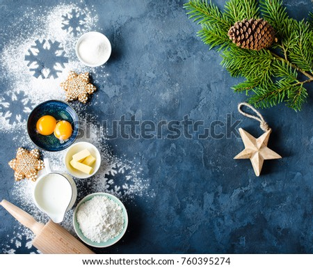 Christmas/New Year food background. Baking ingredients, snowflake cookies, Christmas decoration. Making festive New Year sweets. Flour, rolling pin, gingerbread, milk, eggs. Space for text. Top view #760395274