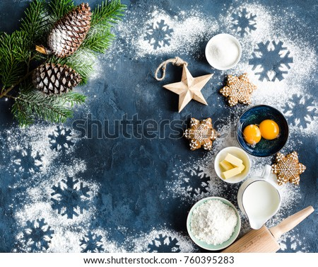 Christmas/New Year food background. Baking ingredients, snowflake cookies, Christmas decoration. Making festive New Year sweets. Flour, rolling pin, gingerbread, milk, eggs. Space for text. Top view #760395283