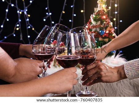 Friends celebrating Christmas or New Year eve party, cheering with wine, christmas lights decoration background, christmas atmosphere. #760407835