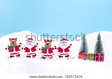 Two Santa Clauses and two reindeer with gifts in the snow