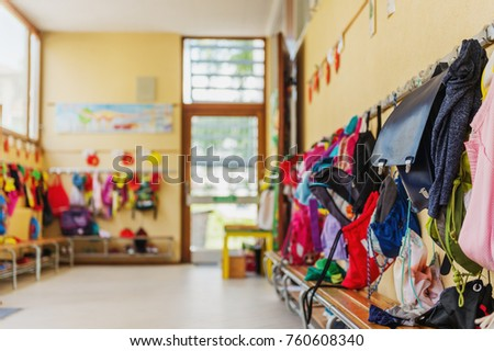 Empty hallway in the school, backpacks and bags on hooks, bright recreation room Royalty-Free Stock Photo #760608340