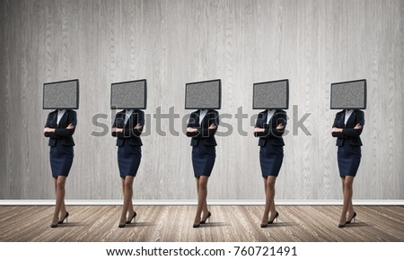 Business women in suits with TV instead of their heads keeping arms crossed while standing in a row in empty room with gray wall on background. #760721491