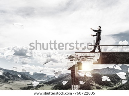 Businessman walking blindfolded on concrete bridge with huge gap as symbol of hidden threats and risks. Skyscape and nature view on background. 3D rendering. #760722805