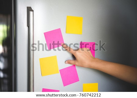 hand holding blank sticky paper note on refrigerator door #760742212