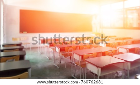 School classroom in selective focus background without young student; Blurry view of elementary class room no kid or teacher with chairs and tables in campus.