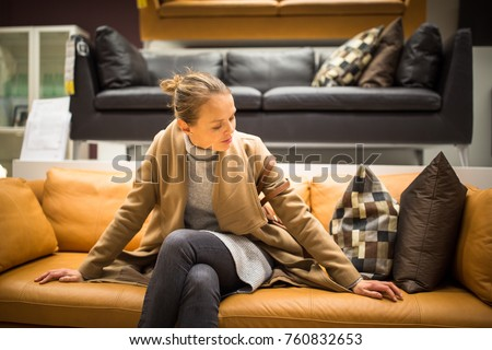 Pretty, young woman choosing the right furniture for her apartme #760832653