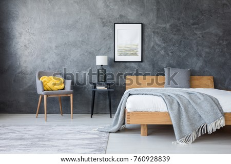 Poster on concrete wall above stool with lamp and wooden bed in dark bedroom with yellow pillow on a chair #760928839