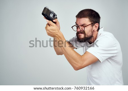 man in a white T-shirt on a light background with an old camera                             #760932166