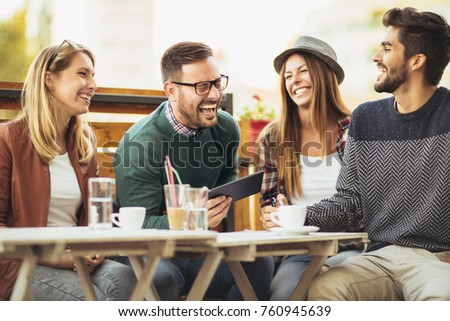 Group of people sitting at outdoor cafe and using digital tablet #760945639