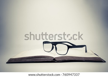 Eyeglasses on an open book with vintage background. #760947337
