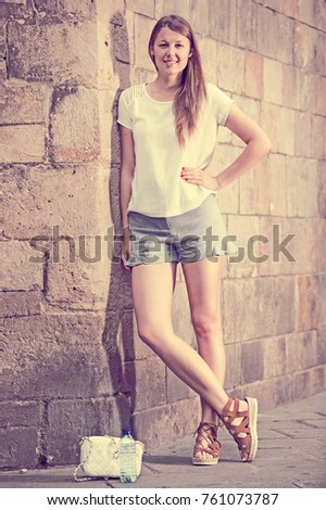 Happy young woman strolling around city standing near old stone wall  #761073787