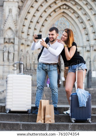 Young family couple of tourists with luggage taking photo on mobile phone #761074354