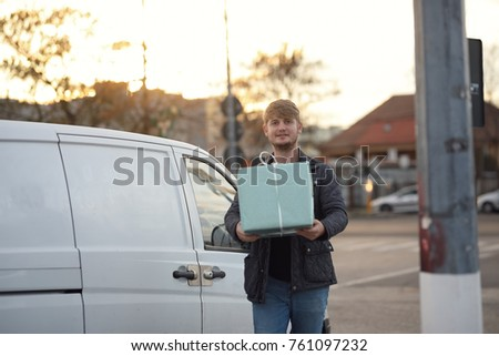 Young boy with a gift box in his hands, delivery outside from his van truck. Gift store order job #761097232