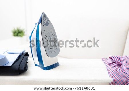 Steam blue iron on ironing board. Clothes, ironing board household concept #761148631