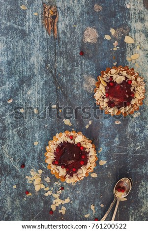 Cranberry  almond tarts on rustic blue surface with large copy space, top view #761200522