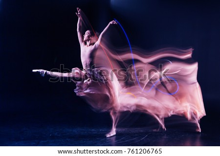 Grace and elegance. Beautiful gracious skillful woman standing on stage and doing some dance movements while showing her performance Royalty-Free Stock Photo #761206765