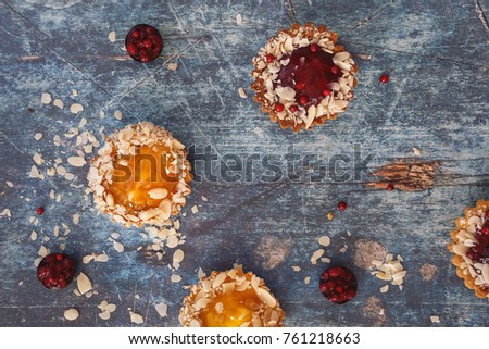 Assorted mini tarts of different sizes on rustic table. Top view, blank space #761218663