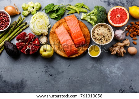 Healthy food clean eating selection: fish, fruit, vegetable, cereal, leaf vegetable on gray concrete background copy space #761313058